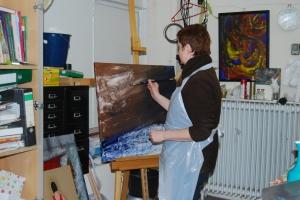 Katharina Iglinski malt den Untergrund ihres Bildes